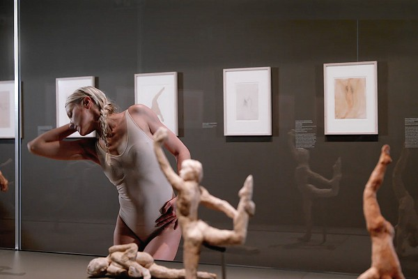 Dancer Noora Kela from Shobana Jeyasingh Dance performing alongside small sculptures of dancers by artist Auguste Rodin